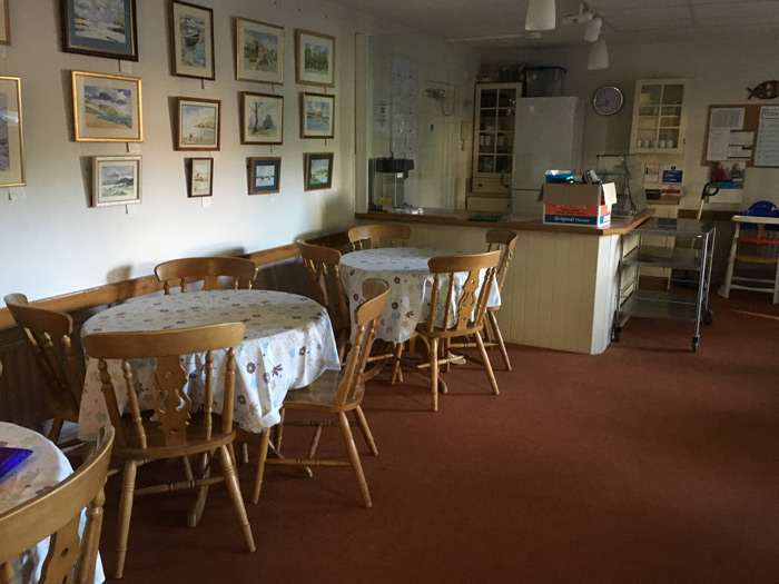 The cafe has seven round tables with tableclothes and four chairs round each. This picture shows three of the tables. There is art on the walls. In the far left corner is a counter for drinks.